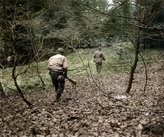 GIs from U.S. First Army hunt German paratroopers dropped during the Bulge, Belgium, Dec. 18, 1944.